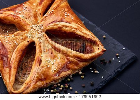 Home made, puff pastry with meat and spices on the black background. Cooking and baker. Tasty and appetizing. Delicious food. Your breakfest or dinner.