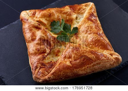 Homemade cheese puff pastries with parsley on black background. Cooking and baker. Tasty and appetizing. Delicious food. Your breakfest or dinner.