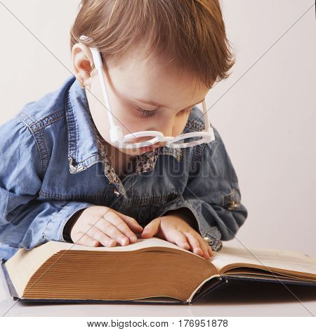beautiful little child girl learns to read (Humorous picture). Science knowledge teaching success self development concept.