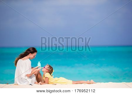 Little daughter applying sun cream to her mother nose