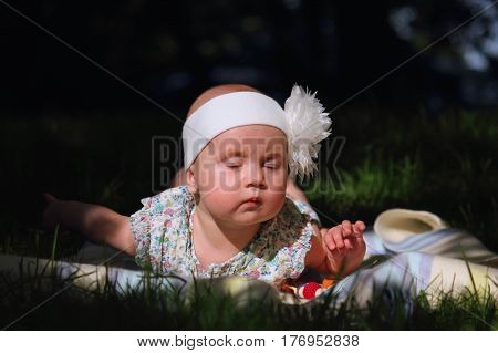 Outdoor recreation. Beautiful tired and sleepy baby girl lying in the shade on the grass. Nature holidays childhood concept.