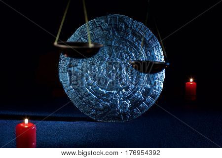 mayan calendar on black background and candles and scales