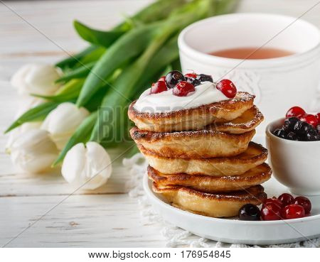 Breakfast. Fritters With Sour Cream And Fresh Berries. Pancakes. A Cup Of Tea, Cranberries, Black Cu