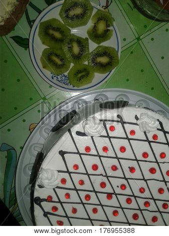 attribute black cake celebration chocolate circles confection constant cream cut decorated decoration dessert dots festive fruit good great green holidays jam kiwi major pieces plate red round side small sweet table the white