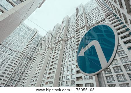 View from bottom of modern contemporary white skyscraper apartment building with regular windows and balconies on bright day with blue