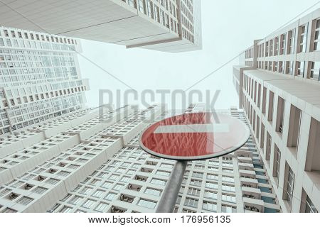 View from bottom of modern contemporary white skyscraper apartment building with regular windows and balconies on a bright day with a red stop road sign reflecting the building Moscow Russia