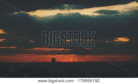 Dramatic dark red and orange scenery of city buildings silhouettes at sunset after storm with massive cloud front and sun god rays shooting from high above in dusk evening