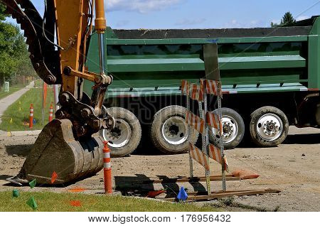 The bucket of an exciting machine is ready too scoop earth into the box of a truck in a street construction project