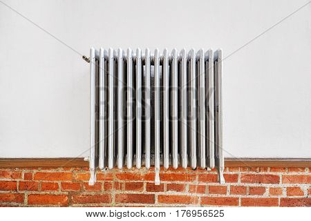 Old heating radiator on a white wall.