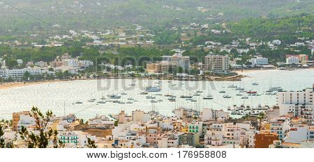 Hill side view of St Antoni de Portmany, Ibiza, on a clearing day in November, kindly warm breeze in autumn,  Marina with moored boats,
