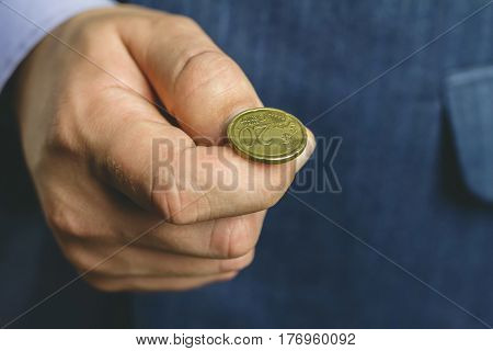 Business man in blue suit holds golden euro cent on hand fingers tossing coin heads or tails game