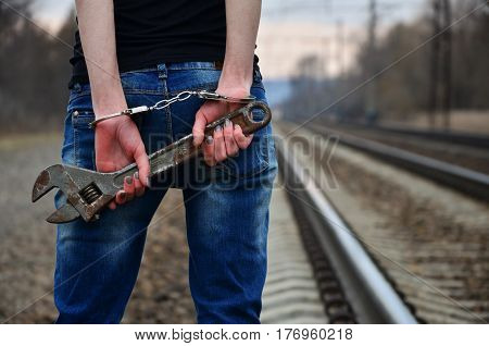 The Girl In Handcuffs With The Adjustable Wrench On The Railway Track Background
