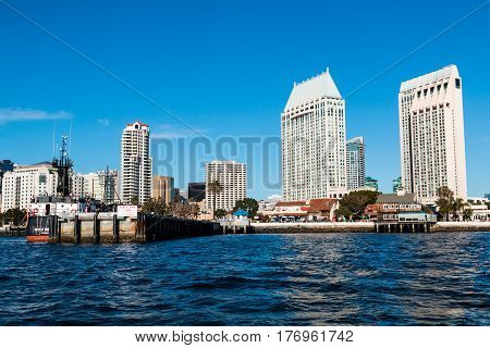 SAN DIEGO, CALIFORNIA - MARCH 2, 2017:  Seaport Village, Tuna Harbor Dockside Market pier, and the downtown San Diego skyline with surrounding hotels.