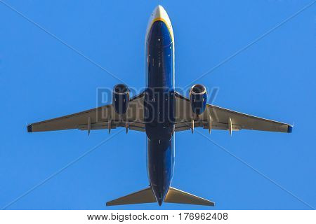 a blue passenger commercial jet plane isolated against the blue sky, taking off blow view.