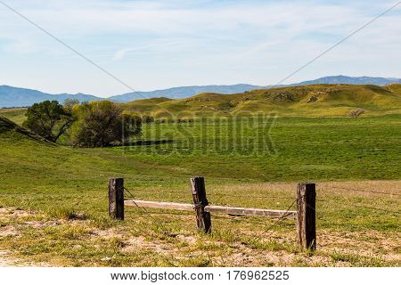 Rolling hills and green pasture with barbed wire fence.