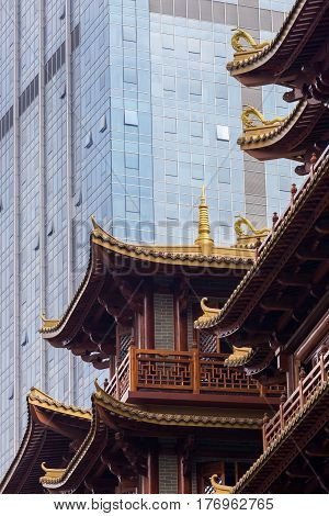 Juxtaposition of old versus new architecture styles: modern skyscraper towering above a traditional chinese building