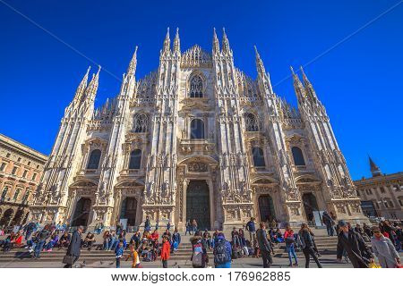 MILAN, ITALY- MARCH 7, 2017: Duomo di Milano Gothic cathedral in Piazza Duomo. Tourists walking and shopping in Milano fashion city.