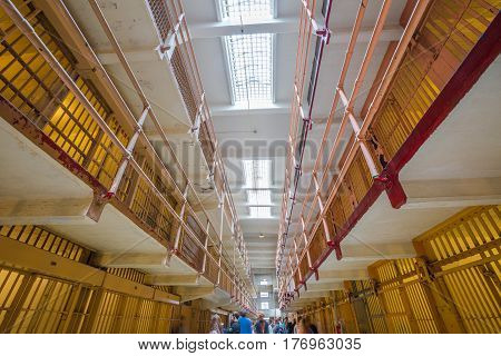 San Francisco, California, United States - August 14, 2016: tourists visiting Alcatraz prison in main corridor upper cells on both sides on three levels. San Francisco is historical site landmark.