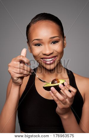 Happy Healthy Black Asian Woman Eating Avocado
