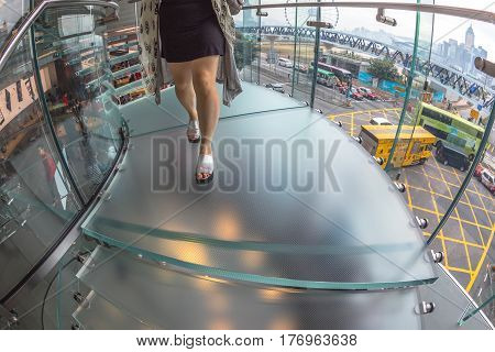 Hong Kong, China - December 4, 2016: fish-eye ground view of woman legs on glass spiral stairway in Apple store, IFC Mall. Victoria Harbour and Central District on background.