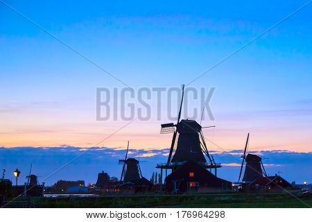Sunset in landscape with mill the Netherlands. Silhouettes of Dutch mills near the lake at sunset in a rural landscape. Dutch mill by evening. Dutch mill by evening.