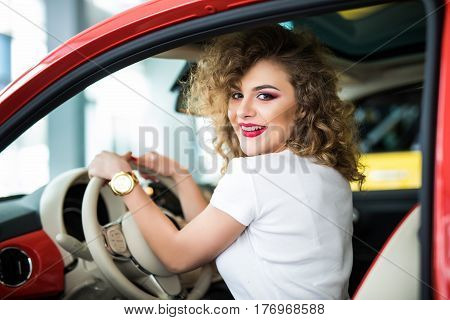 Rear View Of Attractive Young Woman In Casual Wear Looking Over Her Shoulder While Driving A Car