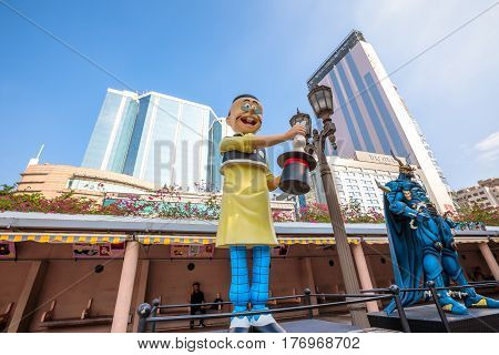 Hong Kong, China - December 5, 2016: Old Master Q and Lord Dragon, statues of famous characters, in Hong Kong Avenue of Comic Stars, Kowloon Park. Urban skyline of Tsim Sha Tsui