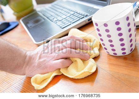 Hand cleaning desk with yellow cloth at home