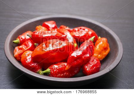 Several red Bhut Jolokia fruit on earthen round plate