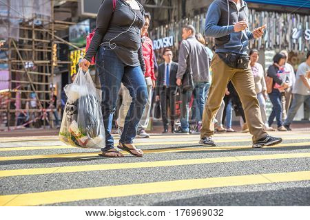 Hong Kong, China - December 6, 2016: woman with shopping bag crossing the street at Yee Wo Causeway Bay, a one stop shop for fashion, luxury and urban stores in Asia