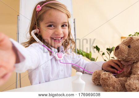 pretty blond Little girl treats a toy bear and making selfie