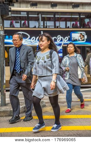 Hong Kong, China - December 6, 2016: An asian family crosswalking the Causeway Bay road of the Yee Wo street, one the busiest downtown for fashion and luxury stores, located on the Henessy road.
