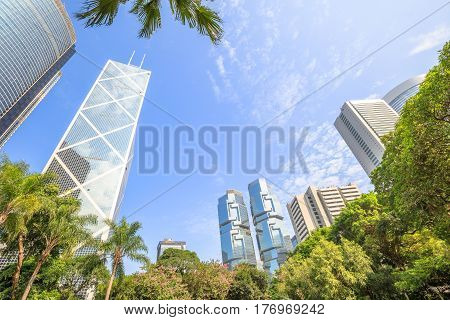 Skyline of modern skyscrapers and towers in the Central business district in a sunny day with blue sky seen from the Hong Kong Park, an oasis of peace in Hong Kong island.