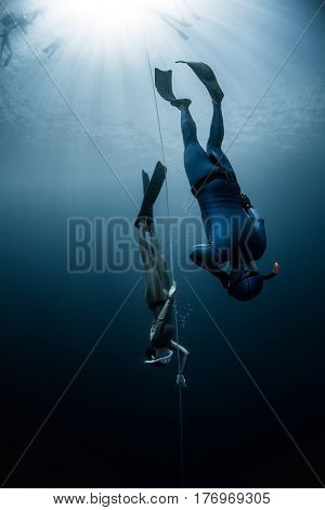 Free diver ascending along the rope in the depth