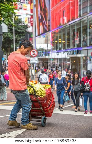 Hong Kong, China - December 6, 2016: asian worker carring his goods on the street market Jardine's Crescent, Causeway Bay, shopping district, full of life and world famous brand shops.