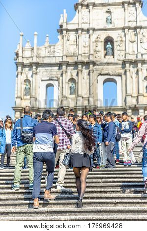 Macau, China - December 8, 2016: couple of tourists on staircase of Ruins of St. Paul's Cathedral, one of the most popular tourist attractions in historic Macau.Iconic stone facade, blurred background