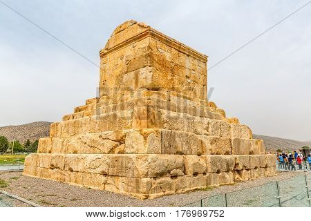 PASARGAD, IRAN - MAY 4, 2015: The group of tourists with the tour guide checking out the tomb of Cyrus the Great.