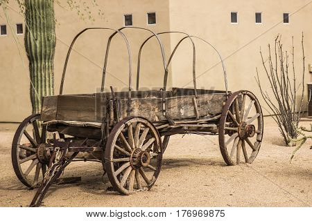 Old Western Wooden Wagon With Hoops In Sand Outside Building