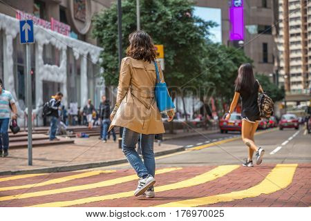 Hong Kong, China - December 6, 2016: Typical Asian woman with bag along the intersection in Times Square, the largest shopping mall in Causeway Bay, the luxury shopping district.