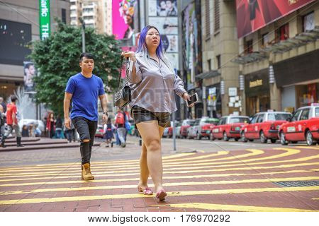 Hong Kong, China - December 6, 2016: Typical modern asian fashion woman with violet hair in Times Square, Causeway Bay, one of most attractive areas for tourists visiting Hong Kong for shopping.