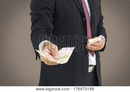 scene of busineesman give the money to you on gray background - can use to display or montage on product or corruption concept