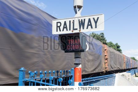 Railway sign and passing cargo train in downtown Tauranga New Zealand.