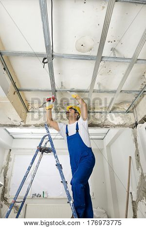 Construction worker wearing overalls and helmet installing drywalls with battery powered screwdriver