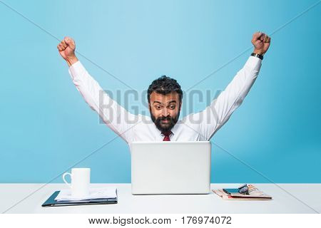 indian businessman and success or victory, indian businessman in beard showing extreme happiness with both hands stretched while sitting and looking at computer screen in the office