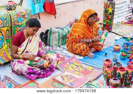 Kolkata West Bengal India - 28th November 2015 : Ladies hand painting vases made of clay handicrafts on display during the Handicraft Fair in Kolkata. Biggest handicrafts fair in Asia.