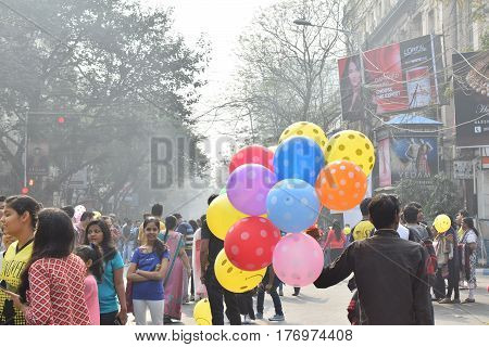 KOLKATA WEST BENGAL INDIA - FEBRUARY 7TH 2016 : Unidentified man selling balloons to city children on blocked otherwise busy Park Street for