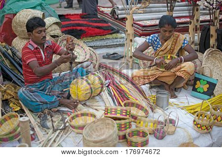 Kolkata West Bengal India - 28th November 2015 : Couple weaving cane baskets handicrafts on display during the Handicraft Fair in Kolkata. Biggest handicrafts fair in Asia.