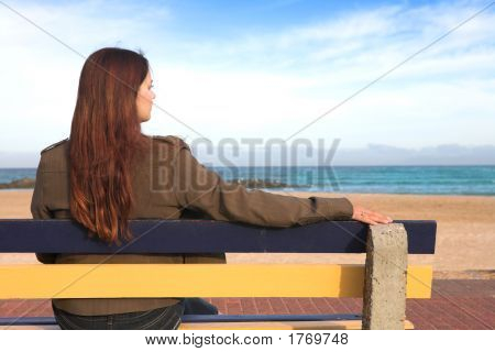 Woman On Bench Next To Sea