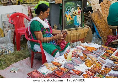 Kolkata West Bengal India - 28th November 2015 : Lady hand coloring idols made of clay handicrafts on display during the Handicraft Fair in Kolkata. Biggest handicrafts fair in Asia.