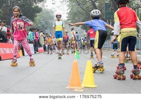 KOLKATA WEST BENGAL INDIA - JANUARY 17TH 2016 : Unidentified city children rollerskating on blocked otherwise busyPark Street for